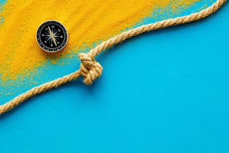 Goal achievement concept. Compass near rope with knot on blue background top view. 写真素材