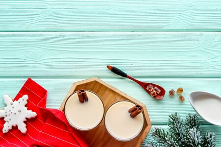 Make festive drink eggnog - ingredients on green wooden background top view frame copy space