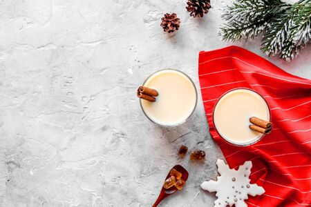 Drink eggnog on grey New Year table decorated with spruce branches and gingerbread top view frame copy space Stok Fotoğraf