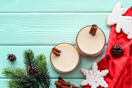 Eggnog - cute New Year composition with alcoholic drink on green wooden background top view frame copy space
