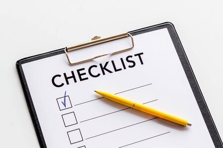 Checklist close up and pen on white background top view