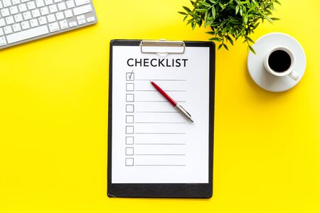 Checklist and pen on yellow office background top view copy space