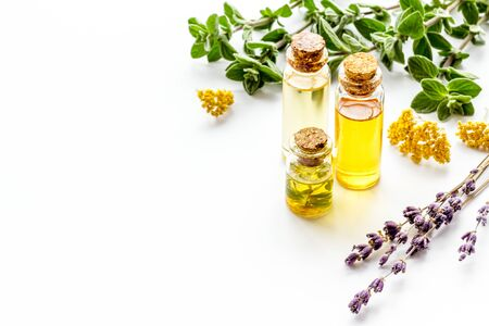 Aromatherapy. Essential oils in small bottles near fresh herbs on white background.