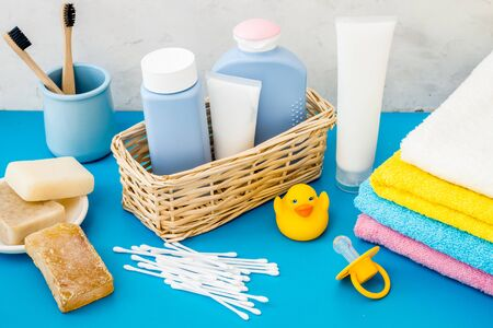 Baby bathroom cosmetics near pacifier and rubber duck on blue background