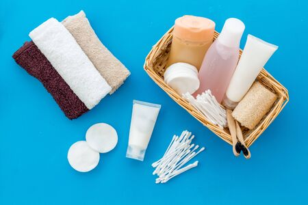 Bathroom cosmetics and hygiene products on blue background top view