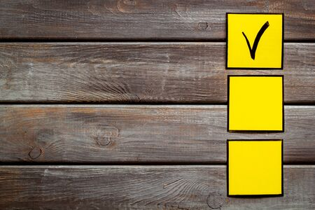 Check mark in yellow check-box on dark wooden background top view copy space