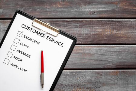 Customer service form on dark wooden background top view copy space