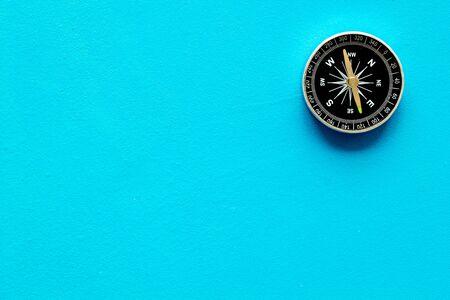 Kompas - klein en stijlvol - op blauwe achtergrond bovenaanzicht kopie ruimte