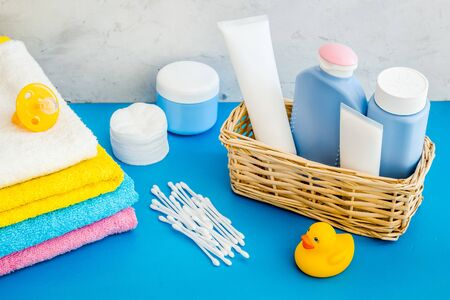 Cute bathroom cosmetics set with yellow rubber duck on blue background. Фото со стока