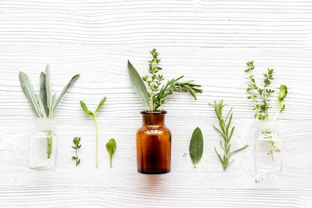 Medicine made from wildflowers and herbs with essential oils on white wooden background top view pattern