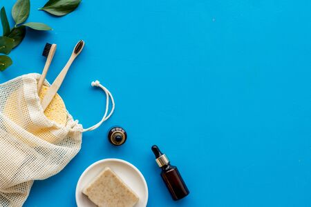 Self-care with herbal formulations - essential oils and soap - on blue background top view copy space