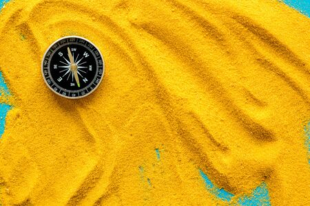 Travel concept. Compass on yellow sand background top view copy space 免版税图像