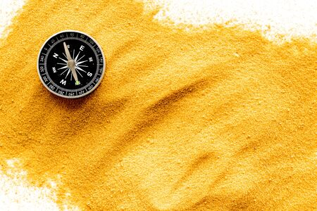 Travel concept. Compass on yellow sand background top view.