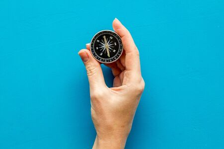 Choose direction concept. Compass in hand on blue background top view copy space 写真素材