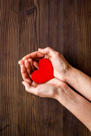 Heart icon. Paper heart in hands on dark wooden background top view copy space Imagens