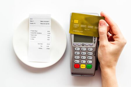 Electronic payments in restaurant. Hand bring bank card to terminal near bill on white background top view Imagens