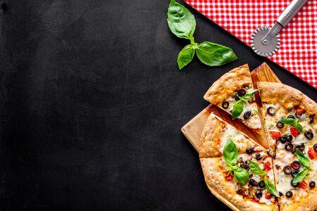 토마토, 바질, 올리브, 치즈가 있는 피자, 텍스트를 위한 검정색 배경 상단 보기 공간