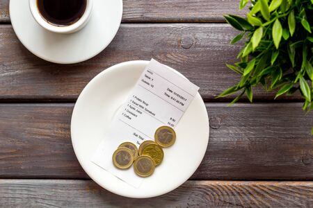 Pay restaurant bill by cash. Reciept and coins on plate on dark wooden background top view