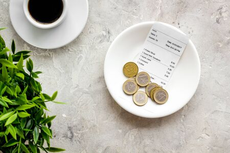 Pay restaurant bill by cash. Reciept and coins on plate on grey background top view Stock fotó