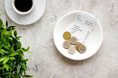 Restaurantrekening contant betalen. Ontvangst en munten op plaat op grijze achtergrond bovenaanzicht Stockfoto