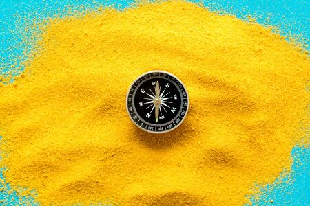Travel concept. Compass on yellow sand background top view copy space 写真素材