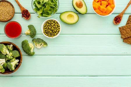 Healthy food. Vegatables and fruits on green wooden background top view frame copy space