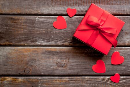 Gift to a sweetheart on Valentines Day. Red present box near hearts on dark wooden