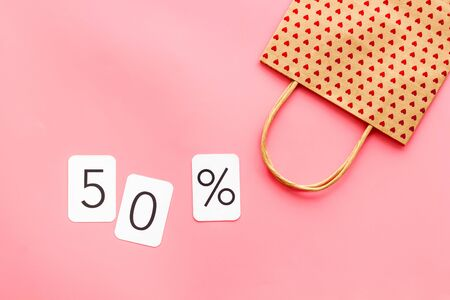 50 off discount sale concept with shopping paper bag on pink