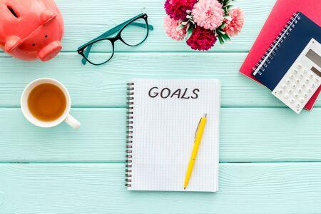 Concepto de plan. Texto de metas en cuaderno en blanco en maqueta de arriba hacia abajo de escritorio de oficina de madera verde