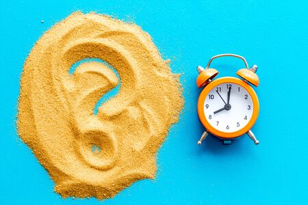 Deadline concept. Clock near question mark on sand on blue background top-down