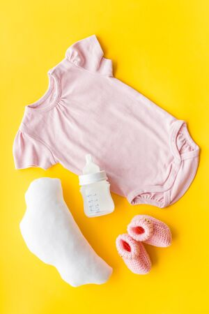 Pink bodysuit for baby girl near childrens things on yellow background top-down