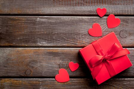 Gift to a sweetheart on Valentine's Day. Red present box near hearts on dark wooden background top-down.