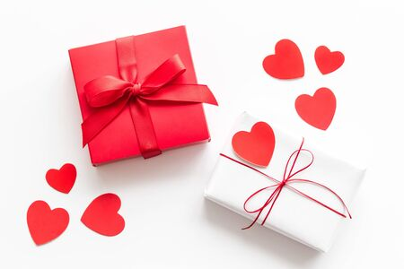 Present to a lover on Valentine's Day. Gift boxes near paper hearts on white background top-down frame.