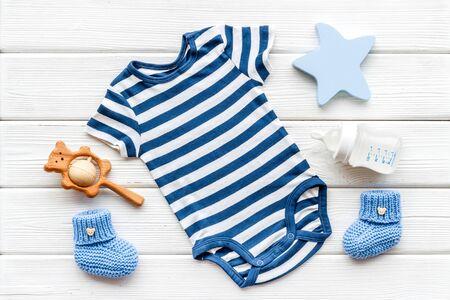 Blue bodysuit for baby boy near children's accessories on white wooden background top-down.