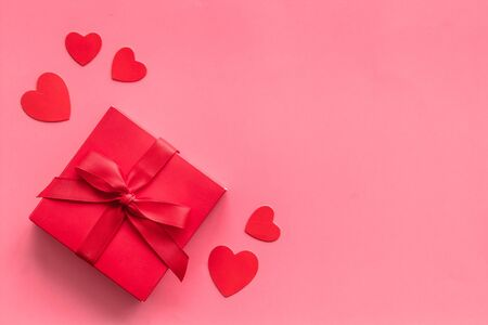 Gift to a sweetheart on Valentine's Day. Red present box near hearts on pink background top-down.