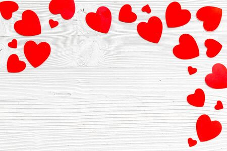 Valentines Day design. Red hearts frame on white wooden background top-down.