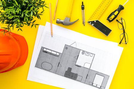 House building plan. Blueprints, instruments, helmet on yellow background top-down. 写真素材