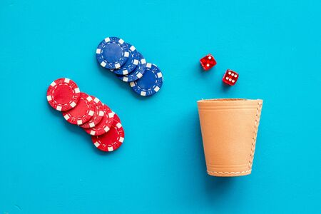 Poker hazard game concept. Chips, dices, cup for dice on blue background top-down