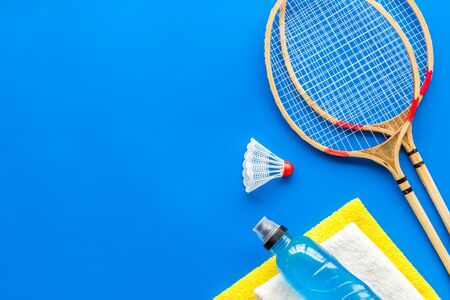 Tennis equipment - rockets, shuttlecock - on blue background top-down frame.