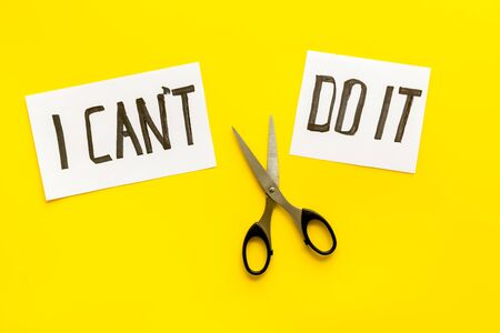 Motivation to self-developing. Cut text I can't do it near scissors on yellow desk. Banco de Imagens