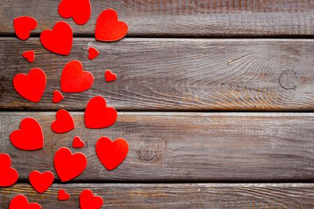 Valentines Day design. Red hearts frame on dark wooden background top-down.