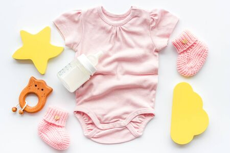 Pink bodysuit for baby girl near children's things on white background top-down.