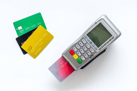 Pay by card. Plastic card inserted in terminal on white background top-down.