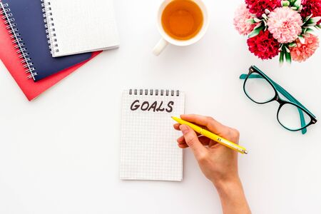 Plan concept. Goals text in blank notebook on white office desk top-down.
