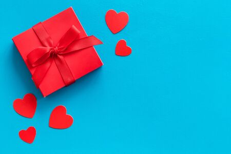 Gift to a sweetheart on Valentine's Day. Red present box near hearts on blue background top-down.