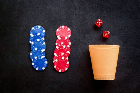 Poker hazard game concept. Chips, dices, cup for dice on black background top-down.