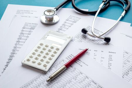 Health insurance concept. Stethoscope near financial documents and calculator on blue background.