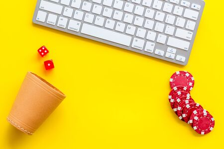 Hazard gemes online concept. Poker chips, dices, cup for dice near keyboard on yellow background top-down. Banque d'images