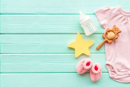 Baby background - pink color. Clothes, booties and accessories for newborn girl on green wooden table top-down frame copy space