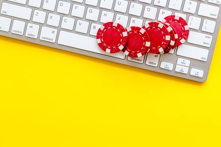 Online poker. Chips near keyboard on yellow background top-down copy space